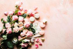 Dekorativ bild av rosor och macroons mot en rosa bakgrund