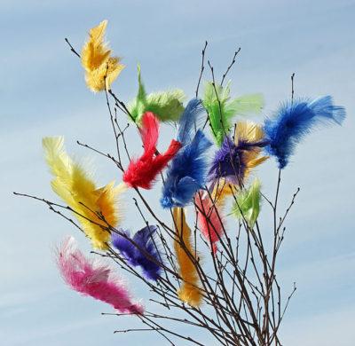 Påskris med färgglada påskfjädrar. (dekorativ bild)